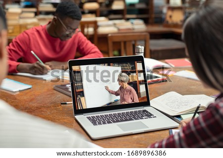 Student watching education tutorials on laptop. Senior teacher teaching math online while student watching her on laptop and taking notes. University students learning trough a webinar on computer.