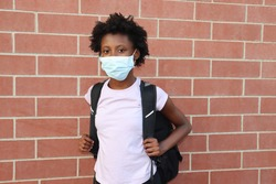 Student wearing surgical face mask and backpack outdoors