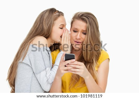 Student whispering to her friend who's texting on her phone against white background #101981119