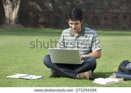 Student with a laptop sitting in a park