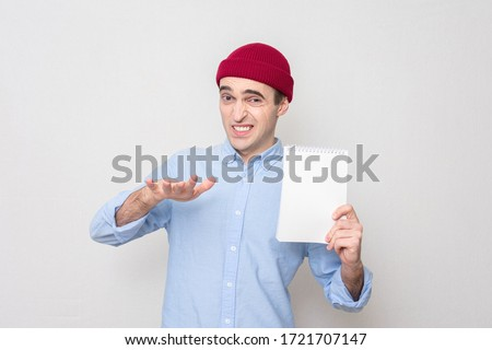 Photo of  Student with a Notepad shows a gesture so-so, white background, portrait