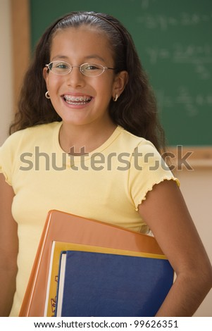 Student with books smiling for the camera