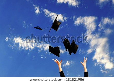 Student with congratulations throwing graduation hats in the air celebrating