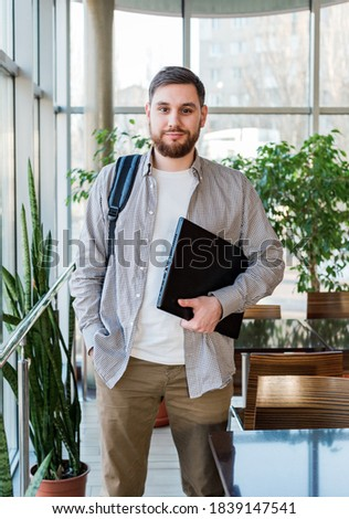 Student with laptop and backpack near window in reopen university campus. Caucasian teenager, confident bearded man carrying laptop in library. Freelancer in modern coworking office with plants. stock photo