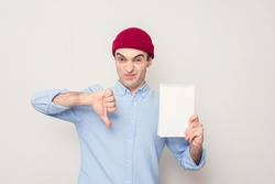 Student with Notepad shows the symbol of the fiasco, white background, portrait, copy space