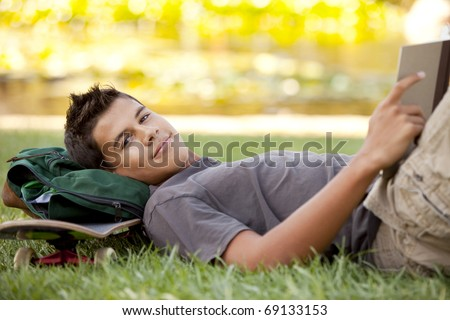 Student with skateboard and backpack reading in the grass - stock photo