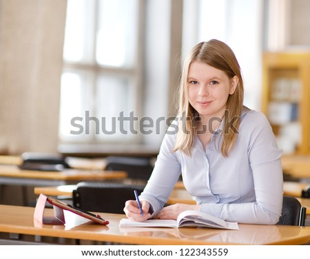 student with touchpad in library. looking at camera