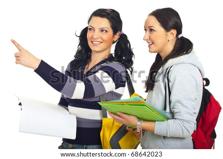 Student woman pointing away and showing something to her colleague isolated on white background