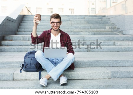 Student working with laptop and cheering to camera with coffee, preparing for exams or having rest in university campus outdoors. Technology, education and remote working concept, copy space