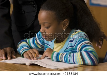 Student works in her workbook as teacher look over her shoulder