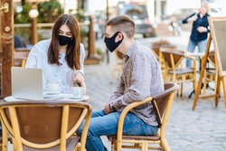 Student youth hipster man and young woman in facial masks drinking coffee at an outdoor bar cafe or restaurant. New normal concept reopening after quarantine concept.