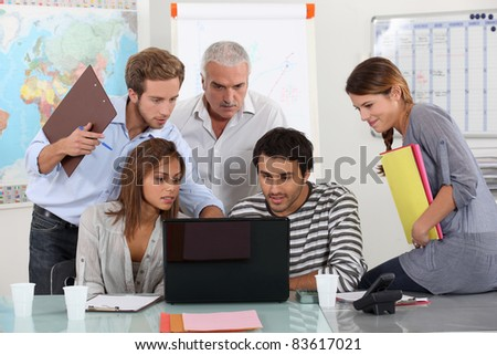 Students and teacher gathered around laptop computer - stock photo