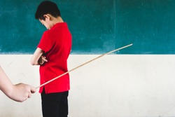 Students being physically punished by teacher with small wooden stick