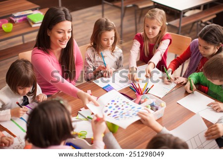 Students boys and girls sitting together around the table in classroom and drawing. With them is their young and beautiful teacher. She teaches children and is smiling