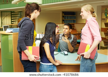 Students chatting while checking out books in library