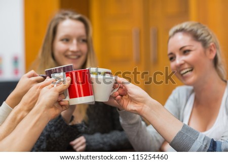 Students clinking cups while smiling in college