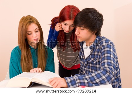 Students concentratedly sitting around a book