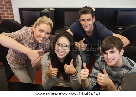 Students giving while thumbs up in college computer room
