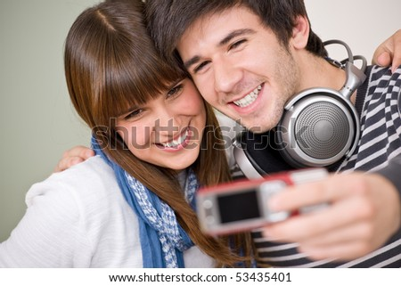 Students - happy smiling teenage couple taking photo with camera