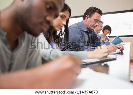 Students in a lecture with one woman looking up in college