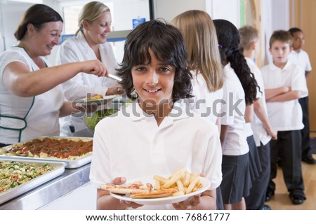 Students in cafeteria line with one holding his unhealthy meal and looking at camera