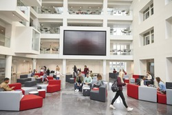 Students in front of screen in atrium of modern university