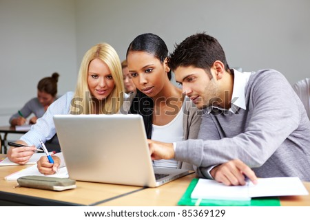 Students in university class learning at laptop