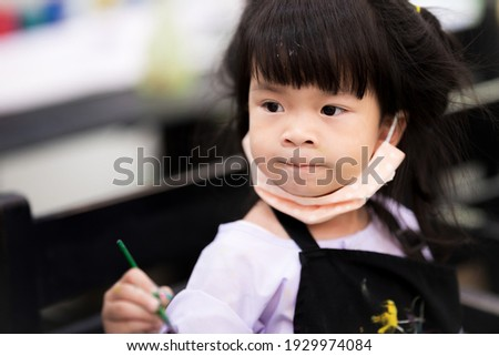 Students intend to study art in class. Children wear a cloth face mask under their chin. Child put on the lips. Kids wear aprons. Cute girl aged 3-4 years old. Stock photo ©