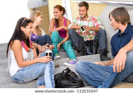 Students laughing on school stairs in break teens college relaxing