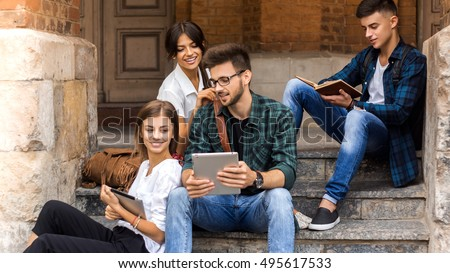 Students life. Low angle view of cheerful young people communicating while holding different gadgets and sitting close to each other on steps.