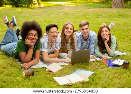 Students Life. Outdoor Portrait Of College Friends Preparing For Exam Together With Laptop And Workbooks, Lying on Lawn At Campus Stock photo ©