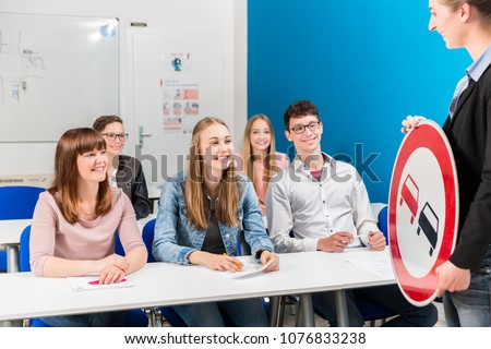 Students listing to their teacher in driving class learning