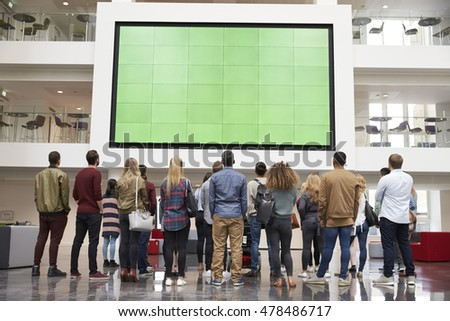 Students looking up at a big screen in university building stock photo