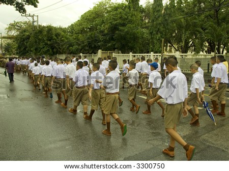 students marching long in the street wearing uniforms
