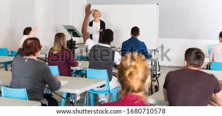 Students of different age sitting together at tables, doing group study with teacher in classroom