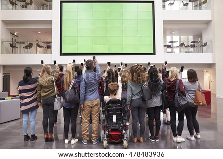Students photograph screen with phones, back view full length stock photo