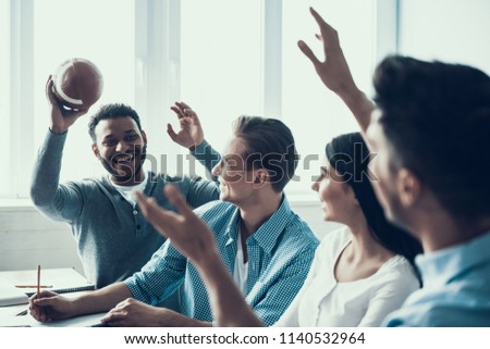 Students Playing with Rugby Ball in Classroom. Multiethnic Team. Indoor American Football. Rugby Player. Playing Together. Football Equpment. Friends in Classroom. Game in Classroom.