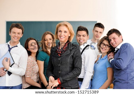 Students posing with their teacher in front of a blackboard