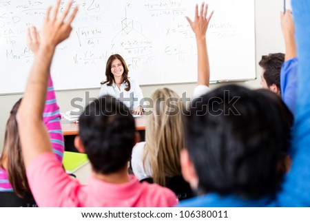 Students raising their hands and asking questions to the teacher