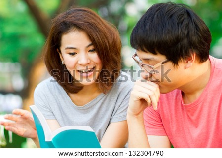 Students reading together in the park.
