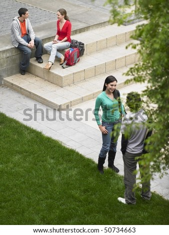 Students sitting and standing on school grounds outdoors, elevated view