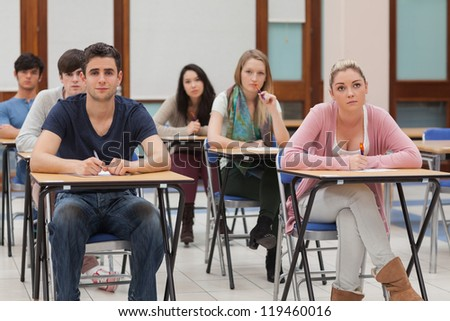 Students sitting at the classroom while listening
