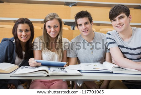 Students sitting at the lecture hall smiling with tablet pc