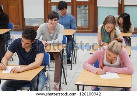 Students sitting in exam room with one boy looking up and smiling