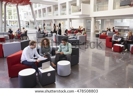 Students sitting in university atrium, three in foreground stock photo