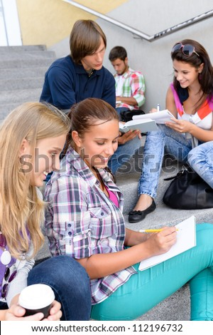 Students sitting on school steps writing studying teens college high-school
