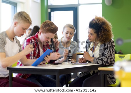 Students sitting with teacher in a lesson. They are using microscopes and a digital tablet.