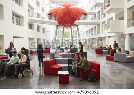 Students socialising in the modern lobby of their university stock photo