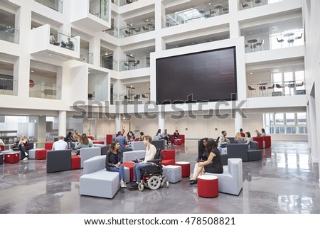 Students socialising under AV screen in atrium at university stock photo
