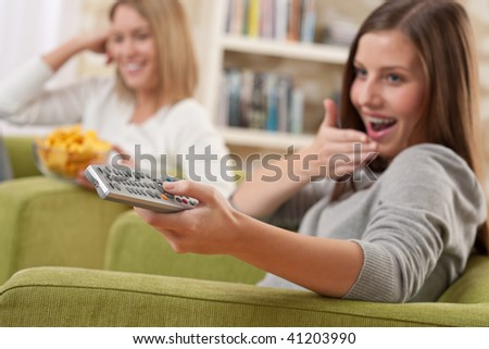 Students - Two smiling female teenager watching television in modern living room, focus on remote control